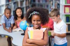 De gelukkige boeken van de meisjesholding tegen klasgenoten stock afbeelding