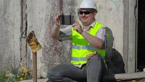 De gelukkige bouwvakker neemt selfie stock videobeelden