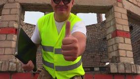 De gelukkige bouwvakker toont duim stock footage