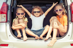 De gelukkige broer en zijn twee zusters zitten in de auto royalty-vrije stock afbeeldingen