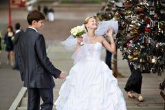 De gelukkige bruid en de bruidegom bij huwelijk lopen op brug Royalty-vrije Stock Foto