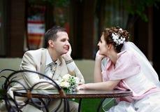 De gelukkige bruid en de bruidegom zitten bij lijst in koffie Stock Foto
