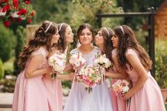 De gelukkige bruid met de boeketten van de bruidsmeisjegreep en heeft buiten pret Mooi bruidsmeisje in zelfde kledingstribune doo stock afbeelding