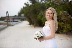 De gelukkige bruid met boquet van witte bloemen op het strand van toevlucht van het luxe de tropische kuuroord is klaar voor de h stock afbeelding