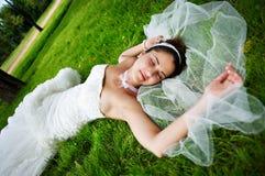 De gelukkige bruid is op gras Royalty-vrije Stock Afbeelding