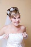 De gelukkige bruid zet op kleding Royalty-vrije Stock Foto