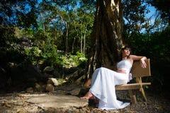 De gelukkige bruid zit op een bank in het park royalty-vrije stock foto's