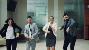 De gelukkige commerciële teammannen en de vrouwen dansen bij het werkpartij die samen organismen, het lachen en het zingen binnen stock footage