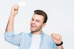 De gelukkige creditcard die van de mensenholding in hand en aan camera kijken Stock Foto