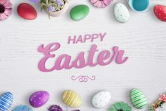 De gelukkige 3D tekst van Pasen op wit houten die bureau met de de kleurrijke eieren en bloemen van Pasen wordt omringd Royalty-vrije Stock Foto