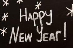 De gelukkige die groet van het Nieuwjaarbericht op een bord wordt geschreven Stock Afbeeldingen
