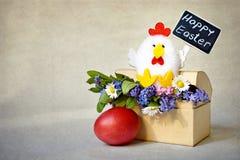 De gelukkige die Pasen-tekst op bord, Pasen-kippenstuk speelgoed en de lentebloemen wordt geschreven schikte in giftvakje Royalty-vrije Stock Afbeeldingen