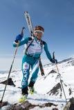 De gelukkige die skibergbeklimmer beklimt aan berg met skis aan rugzak worden vastgebonden Royalty-vrije Stock Foto