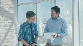 De gelukkige Directeur bespreekt project met werknemer in nieuw modern bureau stock video