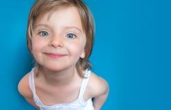 De gelukkige dochter die van het blondemeisje met blauwe ogen bij camera op kleurrijke achtergrond glimlachen Gelukkig ontspannen Royalty-vrije Stock Foto