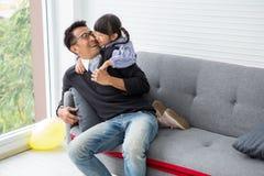 de gelukkige dochter en de vader van het familie Leuke meisje koesteren en spelend op bank in woonkamer besteed thuis tijdvakanti royalty-vrije stock foto