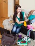 De gelukkige donkerbruine koffers van de vrouwenverpakking Royalty-vrije Stock Fotografie