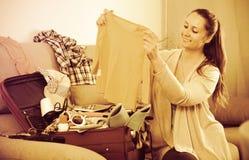 De gelukkige donkerbruine koffers van de vrouwenverpakking thuis Royalty-vrije Stock Foto