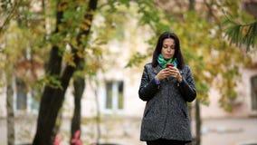De gelukkige donkerbruine vrouw bevindt zich in een park en gebruikt een smartphone stock videobeelden