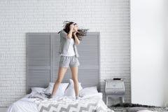 De gelukkige donkerbruine vrouw draagt grijze pyjama's Klok als koffiekop, krant en pen stock foto's