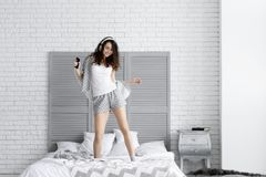 De gelukkige donkerbruine vrouw draagt grijze pyjama's Klok als koffiekop, krant en pen stock afbeeldingen