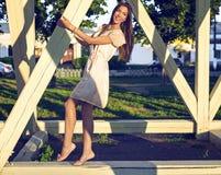 De gelukkige donkerbruine vrouw in een kledings ontspannende pret in het park die op houten stapels in leunen geniet van uw vakan Royalty-vrije Stock Afbeelding