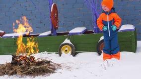 De gelukkige dorpskinderen spelen rond kampvuur van takken tegen achtergrond van stuk speelgoed piraatschip De kinderen zijn same stock video
