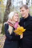 De gelukkige echtgenoot en de vrouw met gele esdoorn leafle bekijken andere royalty-vrije stock fotografie