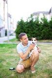 De gelukkige eigenaar loopt met een aanbiddelijke hond en een knuffel van Jack Russell in het groen van het park Het concept vrie stock fotografie