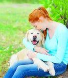 De gelukkige eigenaarvrouw koestert haar Golden retrieverhond op gras Royalty-vrije Stock Foto's