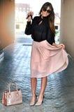 De gelukkige elegante donkerbruine vrouw met zonnebril die een roze dragen plooide rok, zwarte blouse, hoge roze-zwarte hielen, l stock afbeeldingen
