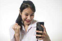 de gelukkige emotionele vrouw, die haar gezicht met genoegengevoel sluiten wekte terwijl het gebruiken van smartphone op royalty-vrije stock fotografie