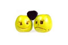 De gelukkige en droevige emoticonsappelen houden suikergoed in de vorm van een hart Gevoel, houdingen en emoties royalty-vrije stock fotografie
