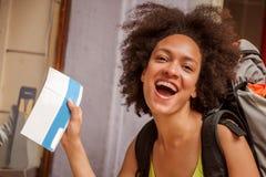 De gelukkige en euforische backpacker vrouwelijke toerist toont kaartje voor hij stock foto's