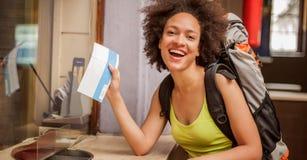 De gelukkige en euforische backpacker vrouwelijke toerist toont kaartje voor hij stock foto