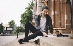 De gelukkige en glimlachende toerist zit op de kerk` s stappen op de straat royalty-vrije stock foto