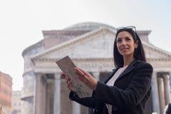 De gelukkige en glimlachende toeristenvrouw houdt een kaart bij het Pantheon in R Stock Afbeelding