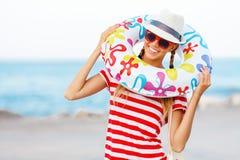 De gelukkige en kleurrijke dragende zonnebril van de strandvrouw en strandhoed die de zomerpret hebben tijdens de vakantie van de Stock Afbeelding
