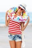 De gelukkige en kleurrijke dragende zonnebril van de strandvrouw en strandhoed die de zomerpret hebben tijdens de vakantie van de Stock Foto