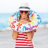 De gelukkige en kleurrijke dragende zonnebril van de strandvrouw en strandhoed die de zomerpret hebben tijdens de vakantie van de Stock Afbeeldingen
