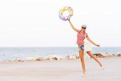 De gelukkige en kleurrijke dragende zonnebril van de strandvrouw en strandhoed die de zomerpret hebben tijdens de vakantie van de Stock Fotografie