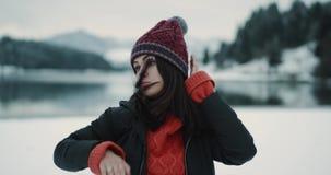 De gelukkige en knappe jonge dame met een rode hoed in het midden van aard in de winterdag het dacing en heeft pret voor stock videobeelden