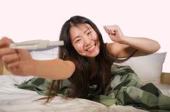 De gelukkige en opgewekte Aziatische Koreaanse de zwangerschapstest die van de vrouwenholding positief zwanger resultaat controle royalty-vrije stock fotografie