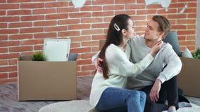 De gelukkige en paarfamilie die genietend van nieuwe samen middelgrote flat snakt schot glimlachen koesteren stock videobeelden