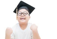 De gelukkige en zeer blije Aziatische gediplomeerde van het schooljonge geitje met graduatie c Stock Fotografie