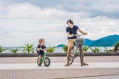 De gelukkige familie berijdt in openlucht fietsen en glimlacht Vader op B Stock Afbeeldingen