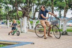 De gelukkige familie berijdt in openlucht fietsen en glimlacht Vader op B Royalty-vrije Stock Afbeelding