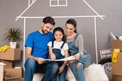 De gelukkige familie bespreekt binnenshuis plan voor regeling van ruimten Concept 6 van onroerende goederen stock fotografie