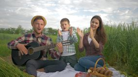 De gelukkige familie, blije papa speelt gitaar terwijl mum met zoon zing en terwijl ontspannend op picknick in aard op groen gebi stock video