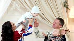 De gelukkige familie, de mammapapa en de kinderen die gelukkig in het huis, weinig baby op handen bij ouders spelen lachen cheerf stock videobeelden
